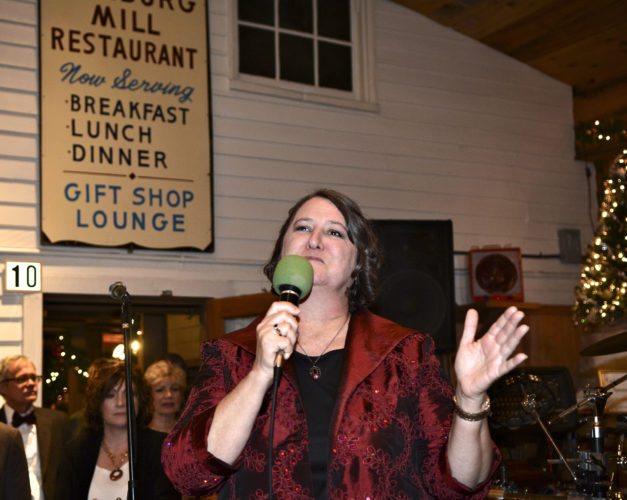 Pam Murphy, executive director of the 3rd Annual Holiday Sparkle Gala & Auction, speaks to attendees last Saturday at the Historic Edinburg Mill. The gala was hosted by the Shenandoah County Free Clinic and Shenandoah Dental Clinic.)  Photo by Andy Starnes